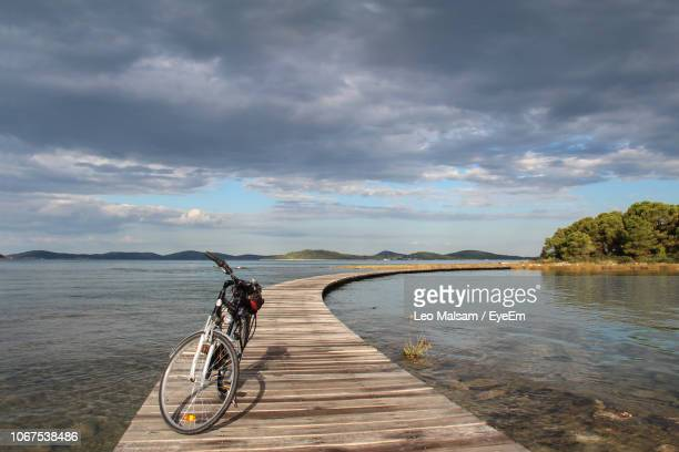 bicycle on boardwalk over lake against sky - human powered vehicle fotografías e imágenes de stock
