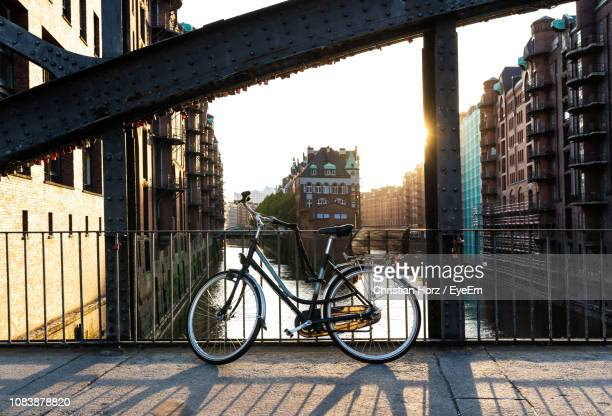bicycle on bridge against buildings in city - man made structure stock pictures, royalty-free photos & images