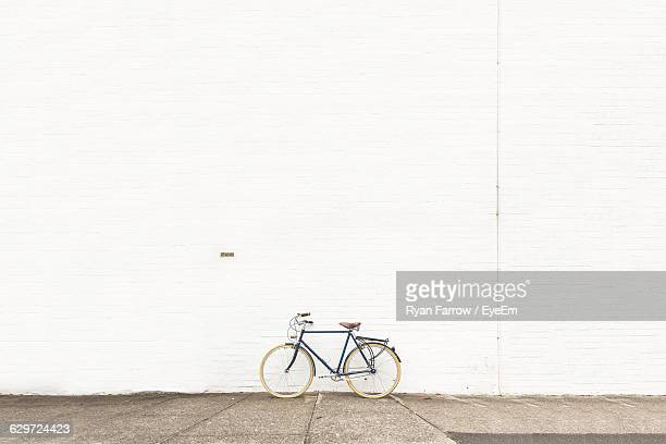 bicycle on street against white wall - muur stockfoto's en -beelden