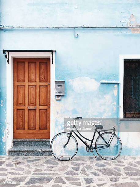 Bicycle parked against blue wall in a village
