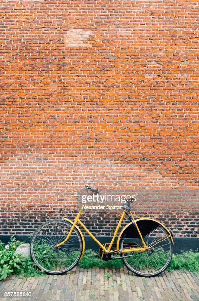 bicycle parked against brick wall - dutch culture stock photos and pictures