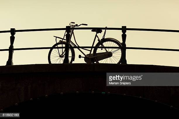 bicycle parked against bridge fence - merten snijders stock pictures, royalty-free photos & images