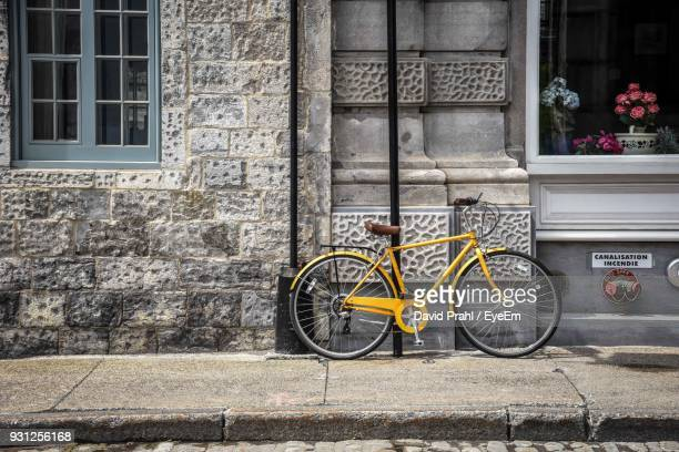 bicycle parked against building at sidewalk - montréal stock pictures, royalty-free photos & images
