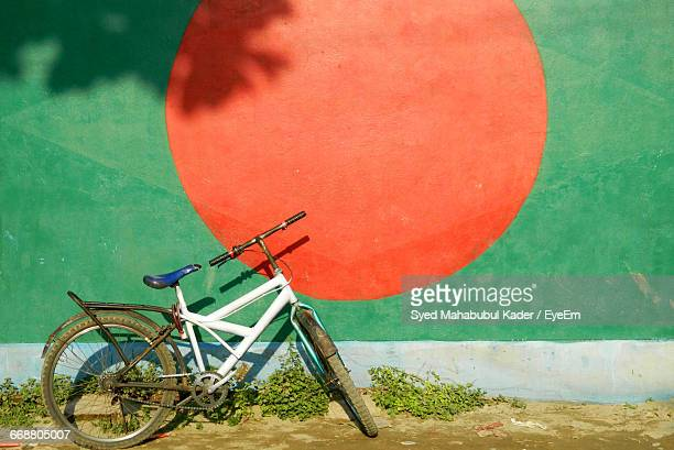 Bicycle Parked Against Flag Of Bangladesh Painted On Wall