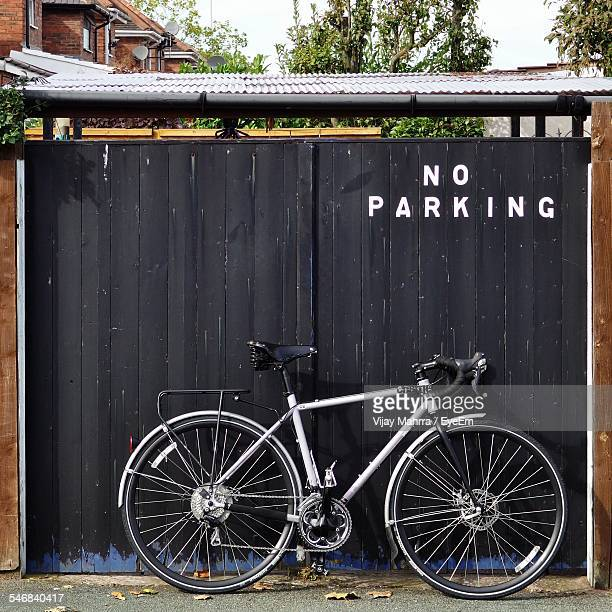 Bicycle Parked Against Gate With No Parking Sign