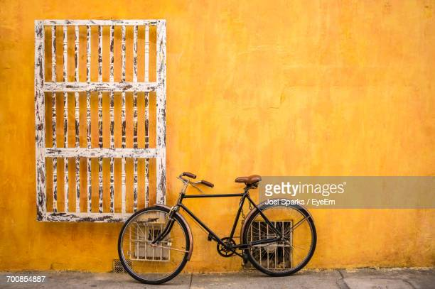 bicycle parked against yellow wall - cartagena colombia foto e immagini stock