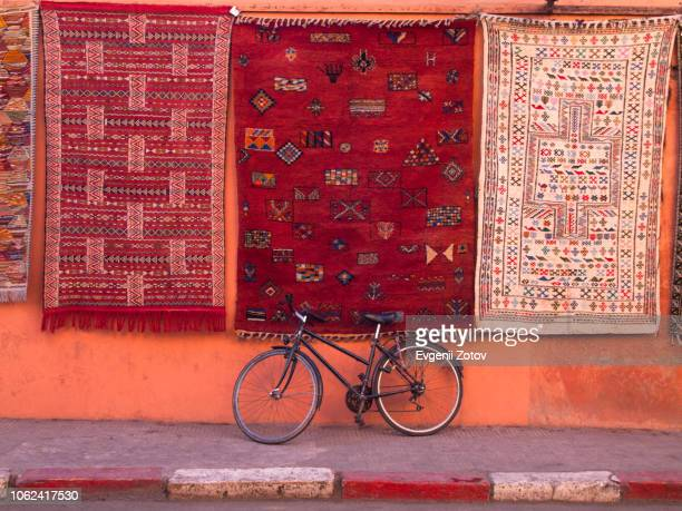 bicycle parked at wall under hanging carpets with traditional patterns. marrakesh, morocco - marrakech photos et images de collection