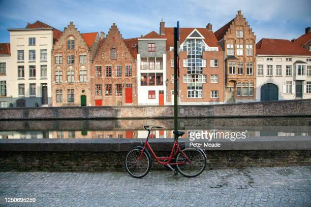 bicycle parked by a canal in bruges - belgium stock pictures, royalty-free photos & images