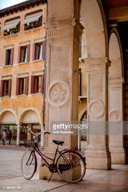 bicycle parked by a column of an old building, treviso, italy - arco architettura foto e immagini stock