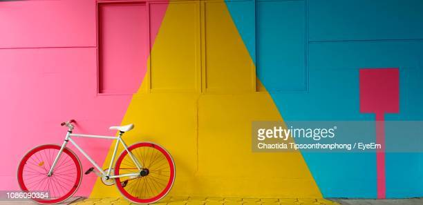 bicycle parked by colorful wall - bunt stock-fotos und bilder