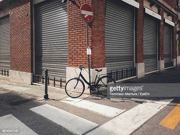 Bicycle Parked By Do Not Enter Sign On Footpath Against Building