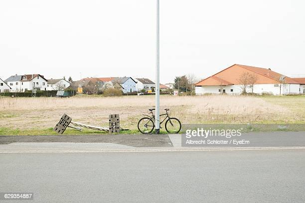 bicycle parked by road - albrecht schlotter stock photos and pictures