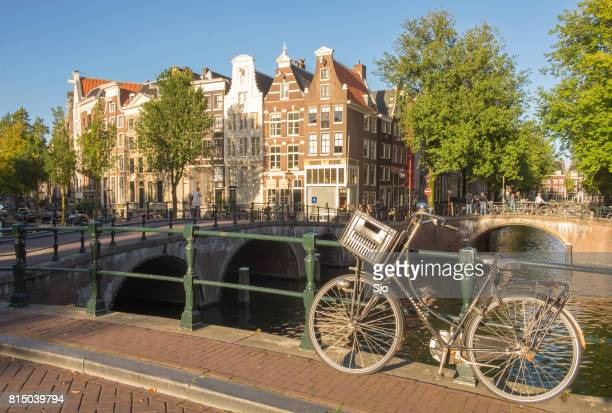 Bicicleta estacionada perto de um canal em Amsterdam, Holanda