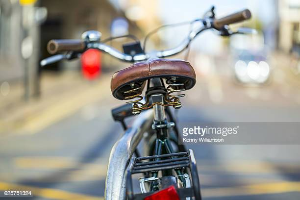 a bicycle parked on a city street - bicycle parking station stock photos and pictures