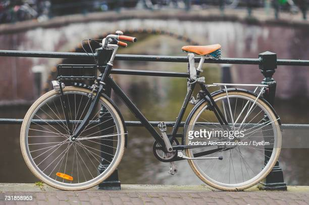 Bicycle Parked On Bridge Over Canal
