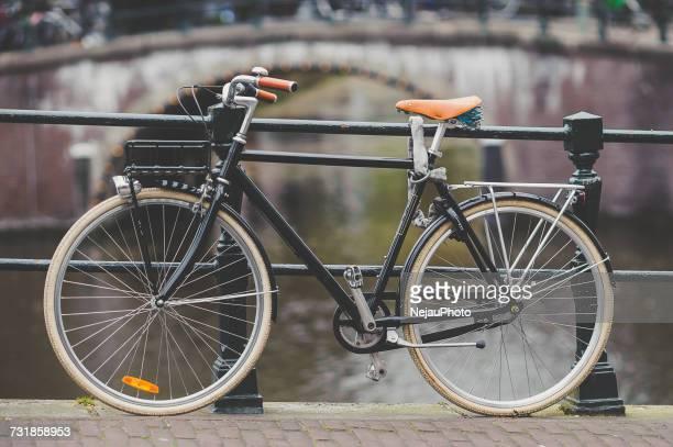 bicycle parked on bridge over canal - niederlande stock-fotos und bilder