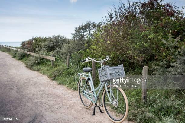 bicycle parked on coastal path, veere, zeeland, netherlands - zeeland stock pictures, royalty-free photos & images