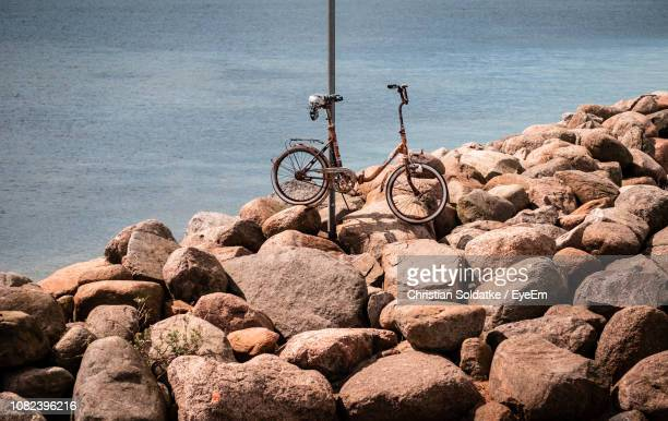 bicycle parked on rocks at beach - christian soldatke stock pictures, royalty-free photos & images