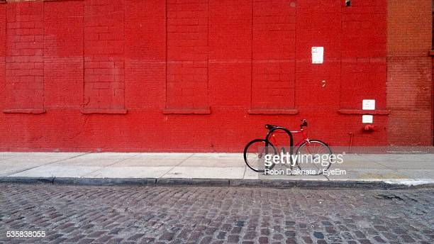 Bicycle Parked On Sidewalk Against Red Wall