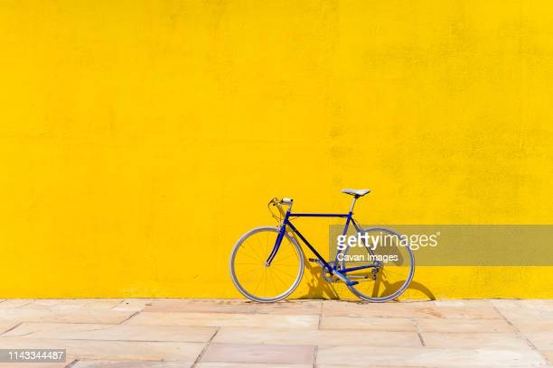 bicycle parked on sidewalk by wall during sunny day - gelb stock-fotos und bilder