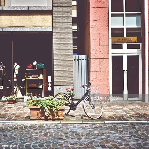 bicycle parked on sidewalk - retail place stock pictures, royalty-free photos & images