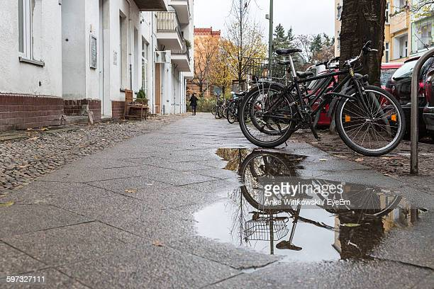 Bicycle Parked On Wet Street By Building