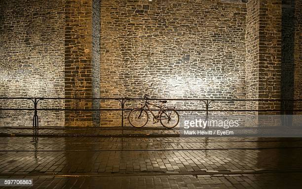 Bicycle Parked On Wet Street By Stone Wall