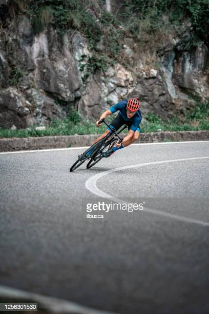 ciclista in bicicletta sulla curva della strada asfaltata - evento ciclistico foto e immagini stock