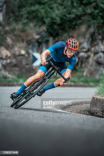bicycle racing cyclist on asphalt road curve - cycling event stock pictures, royalty-free photos & images