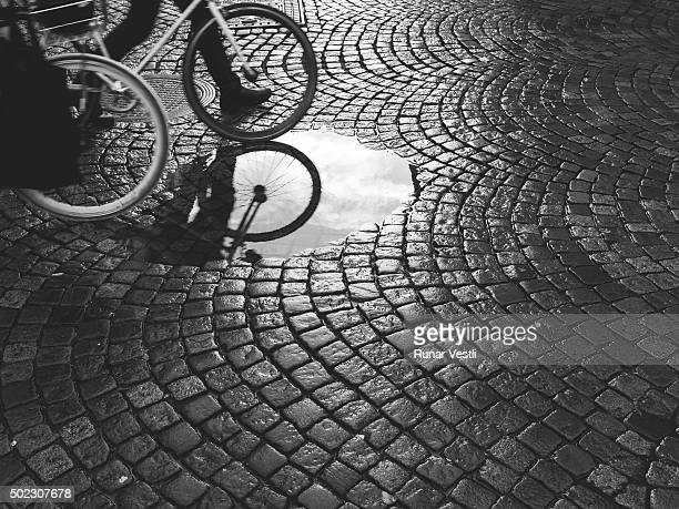 Bicycle reflected in wet cobblestone