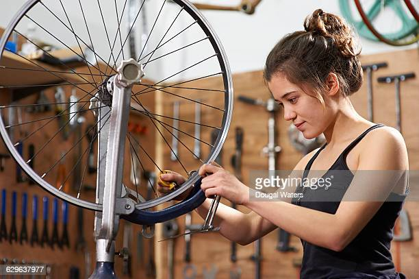Bicycle repairer working in workshop.