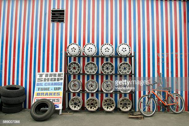 A bicycle rests against a patrioticallypainted redwhiteandblue tire shop wall next to hubcaps and tires offered for sale in the Iron Triangle a...