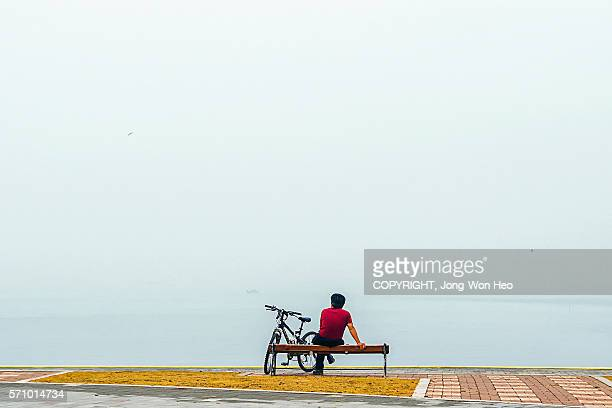 A bicycle rider resting on the bench by the misty sea