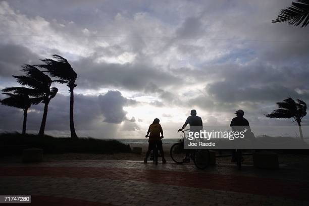 Bicycle riders watch the swirling surf generated by the remains of Tropical Storm Ernesto August 30 2006 in Miami Beach Florida So far the storm has...