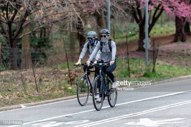Bicycle riders wear a mask in Prospect Park in Brooklyn in the wake of the COVID-19 outbreak on March 20, 2020 in New York City.