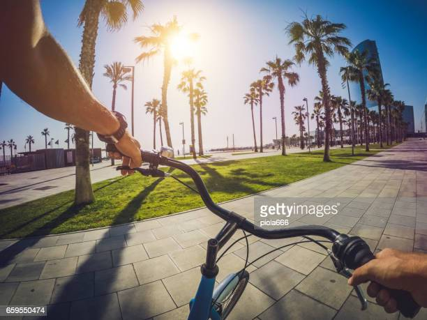 pov bicycle riding at barceloneta beach in barcelona, spain - handlebar stock photos and pictures