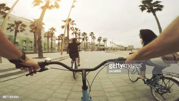 POV bicycle riding with friends at Barceloneta beach in Barcelona, Spain