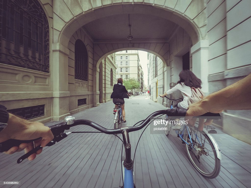POV bicycle riding with two girls in the city : Stock Photo