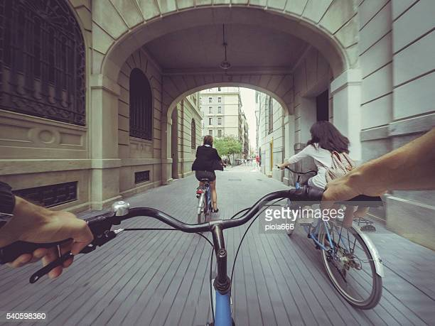 pov bicycle riding with two girls in the city - standpunt stockfoto's en -beelden