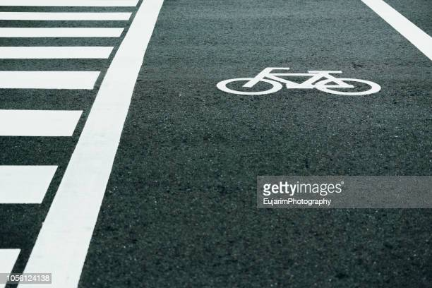bicycle road sign painted on the street next to the pedestrian crossing - bicycle lane stock pictures, royalty-free photos & images