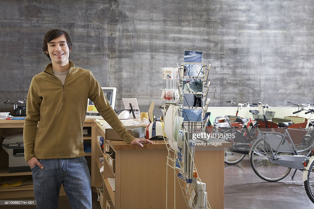 Bicycle shop owner standing at counter, smiling, portrait : Stock Photo