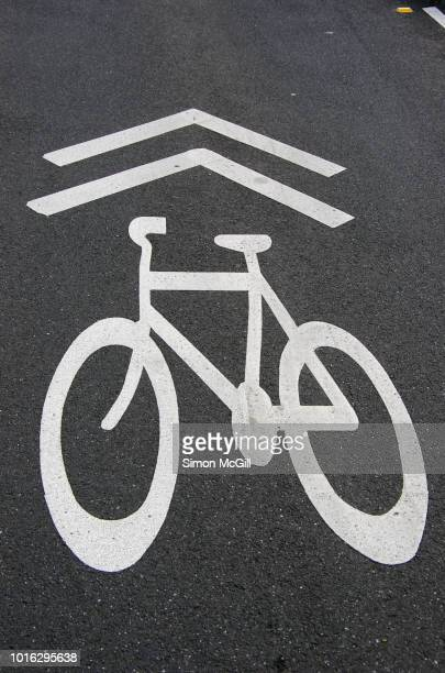 Bicycle symbol and direction arrows stencilled on an asphalt road