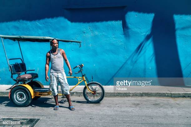 Bicycle taxi driver with his vehicle, Cuba