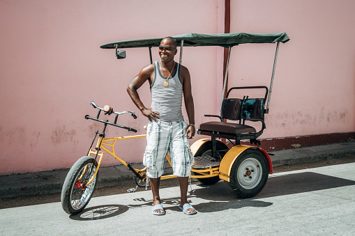 Bicycle taxi driver with his vehicle, Cuba - gettyimageskorea