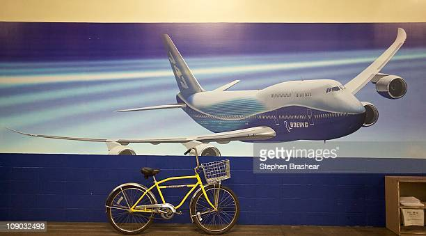 A bicycle used by employees to get around the factory sits below a painting of the 7478 Intercontinental passenger plane at the Boeing factory...