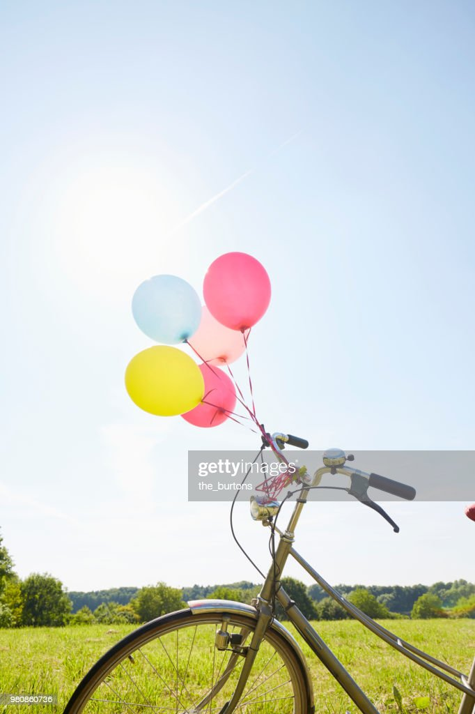 Bicycle with colorful balloons on a meadow against sky : Stock Photo