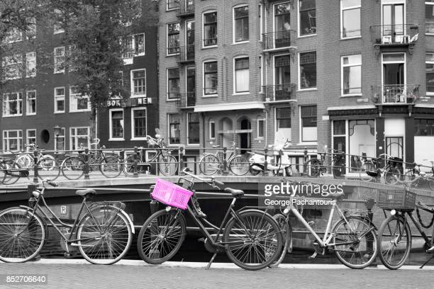 bicycle with pink basket parked on a canal in amsterdam, netherlands - isolated color stock pictures, royalty-free photos & images