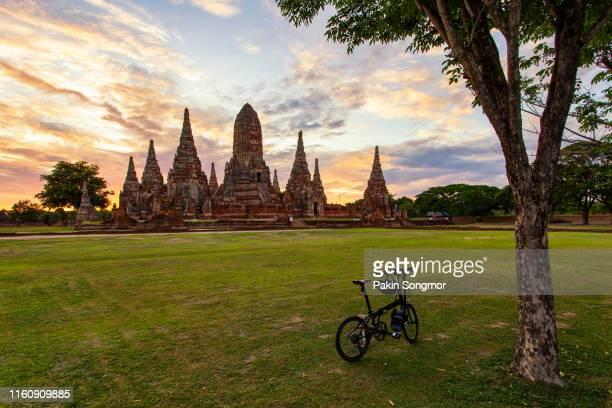 bicycle with wat chaiwatthanaram temple background - sukhothai stockfoto's en -beelden