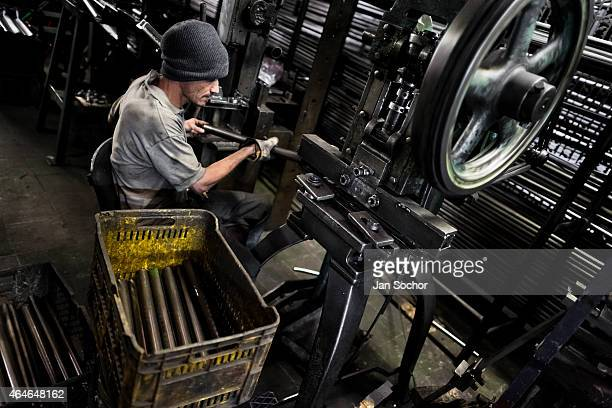 A bicycle worker works on a tube bender machine in a small scale bicycle factory on April 10 2013 in Bogota Colombia Due to the strong vibrant...