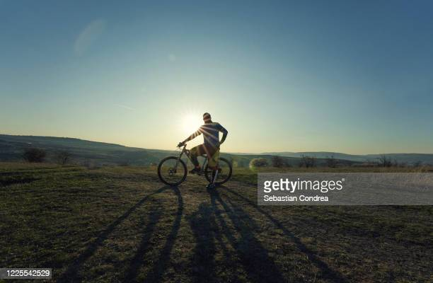 bicycle-man with the bike on sunset background. - vector stock pictures, royalty-free photos & images